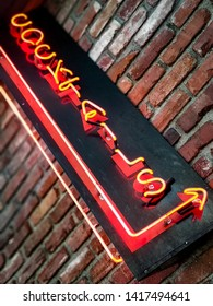 Neon cocktails sign mounted on a weathered brick wall.