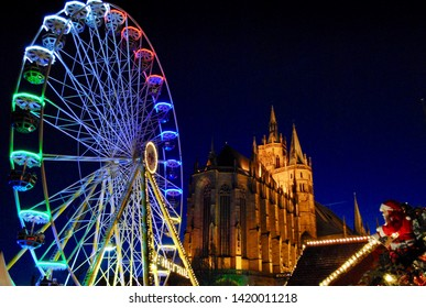 Neon Ferris Wheel illuminates the sky below the St. Mary's Cathedral at the Erfurt, Germany Christmas Market (Erfurter Weihnachtsmarkt).