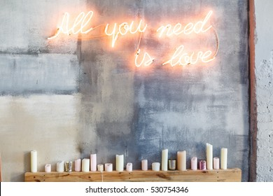 "Neon inscription ""All you need is love"" on a grey concrete wall and many candles under them"