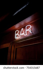 Neon inscription BAR on the wall. Neon inscription BAR in different colors. Multicolored neon inscription BAR on dark background