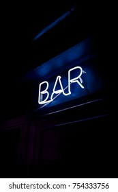 Neon inscription BAR on the wall. Neon inscription BAR in different colors. Multicolored neon inscription BAR on dark background