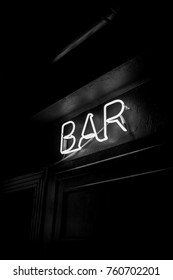 Neon inscription BAR on the wall. Neon inscription BAR in different colors. Multicolored neon inscription BAR on dark background. Black and white photo