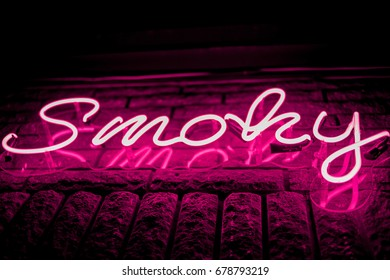Neon inscription SMOKY on the wall. Neon inscription SMOKY in different colors. Multicolored neon inscription SMOKY on dark background