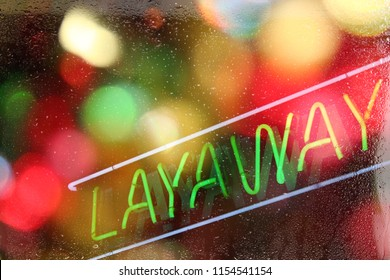 Neon Layaway Sign in rainy window with colorful bokeh