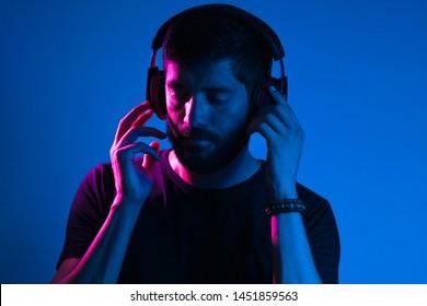 Neon light portrait of bearded man in headphones. Listening to music