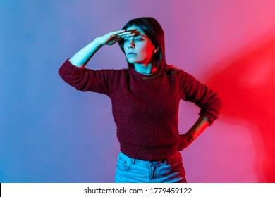 Neon light portrait of concentrated girl keeping hand over eyes looking far away with attentive view, watching horizon, forward future, expectation and exploration concept. indoor studio shot isolated