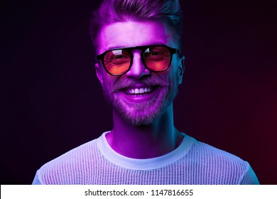 Neon light portrait of smiling man model with mustaches and beard in orange sunglasses and white t-shirt