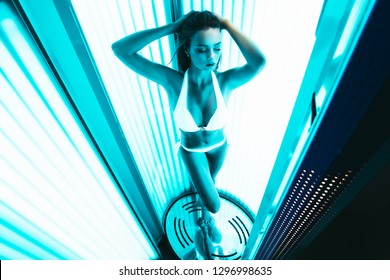 Neon light and sexy girl. Beautiful and athletic woman with naked healthy body standing in solarium spa salon