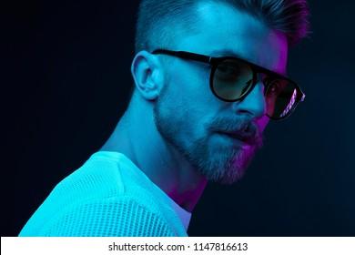Neon light studio close-up portrait of attractive male model in sunglasses and white t-shirt