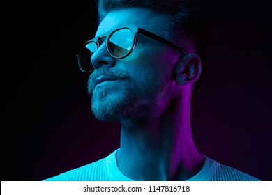 Neon light studio close-up portrait of serious man model with mustaches and beard in sunglasses and white t-shirt