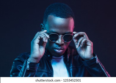 Neon light studio portrait of african american male model wearing trendy sunglasses and leather jacket
