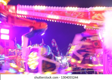 neon lights fairground ride night lights funfair disco synthwave amusement park moving, light trails, slow shutter-speed long exposure illuminations futuristic sci fi stock photo, stock, photograph,