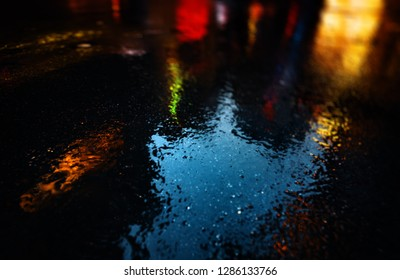 Neon lights in New York City. Lights and shadows of NYC. Streets after rain with reflections on wet asphalt.