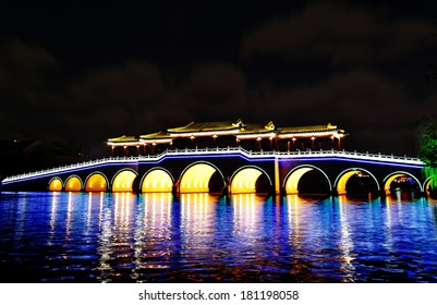 Neon lit ancient oriental architectural bridge with colorful reflection in Suzhou, China.