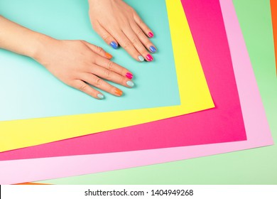 Neon manicure on different multicolored neon backgrounds. Flat lay style.