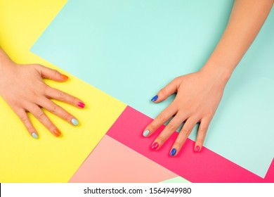Neon manicure on multicolored bright background in trendy colors. Flat lay style.