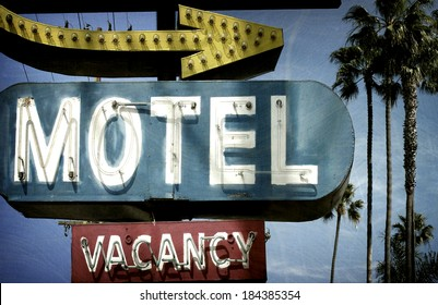 neon motel sign with palm trees