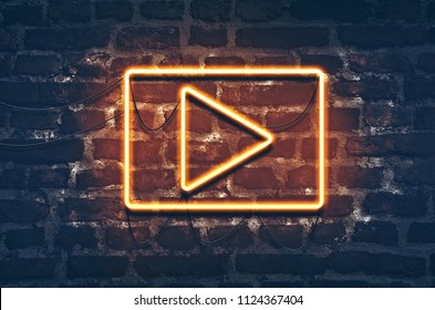 Neon music play sign on dark brick wall background