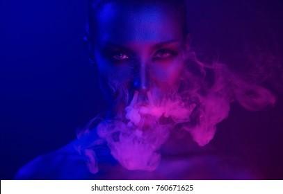 Noche de Neon. Fiesta de Vape de Halloween. Hermosa joven mujer sexy con glamuroso maquillaje místico en Nightclub (exhalando humo). Niña fumando en el Club. Humo místico azul