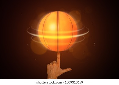 Neon orange basketball ball spinning on a finger on dark background. Games and sports. Outdoor activities. Sporting goods.