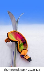 Neon Orange Ski Goggles in Snow with Skis
