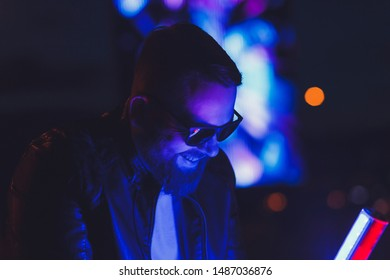 Neon portrait of smiling man model with beard in sunglasses and leather jacket