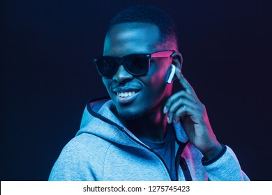 Neon portrait of young african man listening music with wireless earphones
