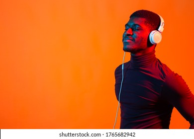Neon portrait of young african man listening music with earphones. Orange background with copy space.