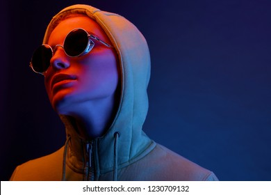 Neon portrait of young woman in round sunglasses and hoodie. Studio shot