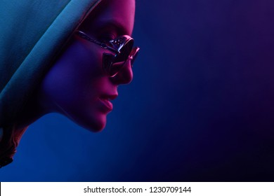 Neon profile portrait of young woman in sunglasses and hoodie. Studio shot with smoke in scene.