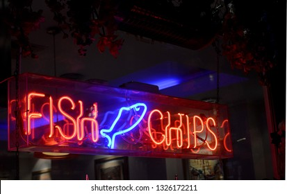 A neon restaurant sign advertising Fish and Chips in London, UK