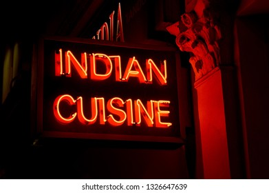 A neon restaurant sign advertising Indian Cuisine in London, UK