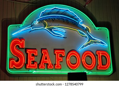 Neon seafood sign at night.