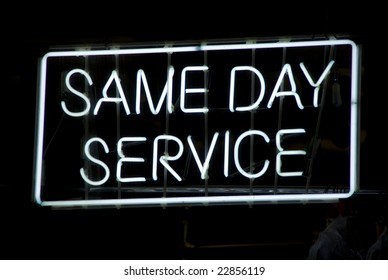 Neon sign advertising same day service in the window of a Harlem, New York City dry cleaning store