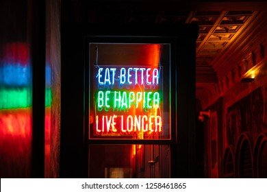 Neon sign, bright glowing advertising. Eat better, be happier, live longer.