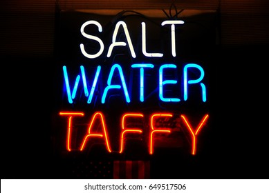 Neon sign hanging in a candy shop window advertising salt water taffy for sale