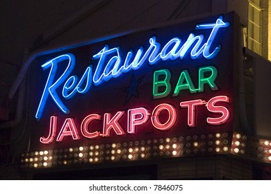 A neon sign outside a restaurant and casino