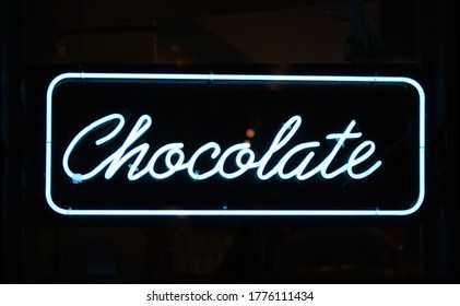 A neon sign reading Chocolate against a black background