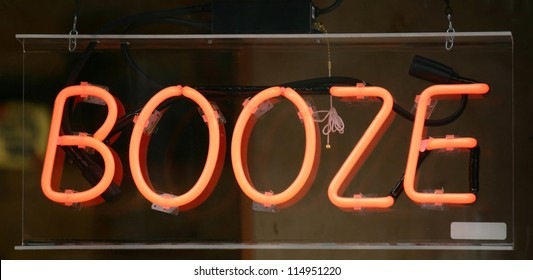 A neon sign in a window that reads Booze