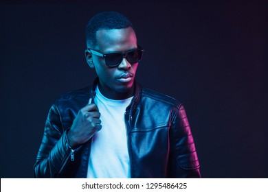 Neon studio portrait of african american man wearing trendy sunglasses and leather jacket