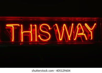 Neon THIS WAY sign; genuine traditional neon sign reading This Way; isolated on black ground