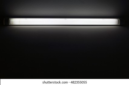 Neon tube light in dark room with copy space for background and design art work.