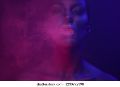 Neon Vape Party, Nightlife. Beautiful Sexy Woman with glamorous makeup vaping in Nightclub neon, exhaling smoke. Girl smoking vaporizer in Club. Blue mystic smoke