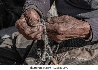 Nepal artisan with weathered hands braiding a rope out of Yak cow skin.