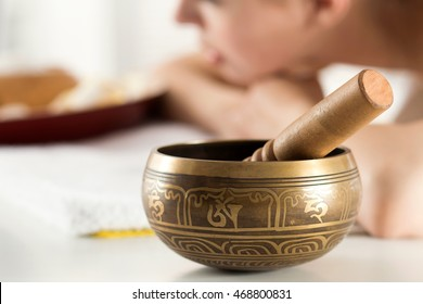 Nepal Buddha copper singing bowl at spa salon with young beautiful woman at background. Sound therapy, recreation, meditation, healthy lifestyle and body care concept