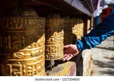Nepal. Everest trekking. Tibetan prayer wheels in Boudhanath. Hand turns the wheel. On wheels hieroglyphs - prayers in Nepali. Om mani padme hum - jewel in the lotus.