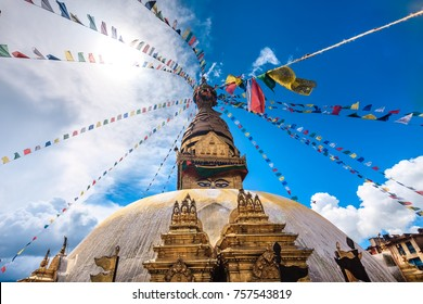 Nepal. Golden Stupa Bouddanath in Kathmandu with colorful Tibetan prayer flags, close-up on a sunny day. Was built in the 14th century. Blue cloudy sky in the background. Travel, holidays, sight