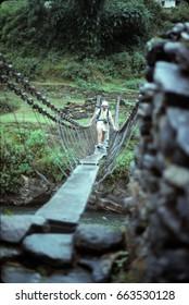 NEPAL HIMALAYAS - OCT 5, 1979 - Trekker on narrow suspension bridge acrosss river near  Those, Nepal, Asia
