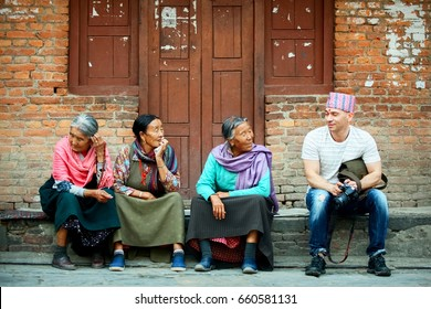 Nepal, Kathmandu, Palace Square - April 26, 2014:  European tourist talks with locals on the street of the old city.