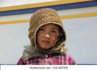 Nepal, May 2017. Little girl in a brown hat on the street of Nepal.
